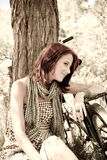 Menina bonita que senta-se perto da bicicleta. Imagem de Stock Royalty Free