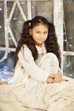 Menina bonita que senta-se perto da janela Imagens de Stock Royalty Free