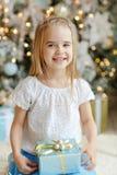 Menina bonita que senta-se perto de uma árvore e dos sorrisos de Natal mim Foto de Stock Royalty Free