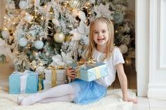 Menina bonita que senta-se perto de uma árvore e dos sorrisos de Natal mim Fotos de Stock Royalty Free
