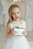 Menina bonita que senta-se perto de uma árvore e dos sorrisos de Natal mim Imagem de Stock Royalty Free