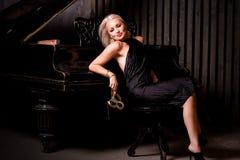 Menina bonita que senta-se perto do piano Fotografia de Stock