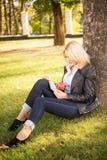 Menina bonita que senta-se sob uma árvore e que lê um livro Foto de Stock Royalty Free