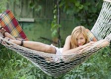 Menina bonita que sorri ao encontrar-se em um hammock Imagens de Stock