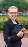 Menina bonita que sorri com portátil Imagem de Stock