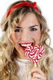 Menina bonita que sorri com uns doces do coração Imagem de Stock