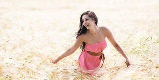 Menina bonita que sorri em um campo de trigo Fotografia de Stock