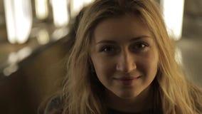Menina bonita que sorri na câmera com a vídeos de arquivo