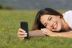 Menina bonita que sorri usando um telefone esperto que encontra-se na grama Imagem de Stock