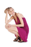 Menina bonita que squatting Fotografia de Stock Royalty Free