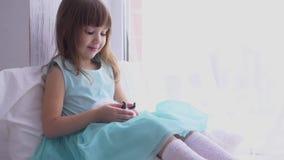 Menina bonita que tem o divertimento, abraçando e jogando com coelho decorativo filme
