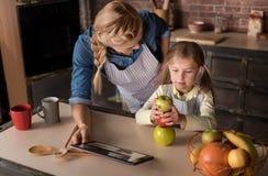 Menina bonita que tem o divertimento com sua mãe na cozinha imagens de stock royalty free