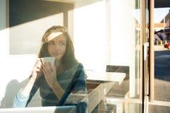 Menina bonita que tem uma ruptura de café na barra imagem de stock