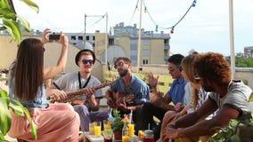 Menina bonita que toma fotos dos amigos no partido em um terraço do telhado vídeos de arquivo