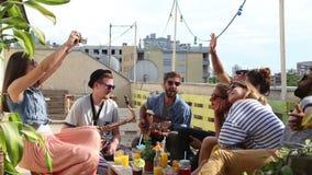 Menina bonita que toma fotos dos amigos no partido em um terraço do telhado filme