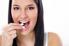 Menina bonita que toma a goma de mastigação branca, sorrindo fotos de stock