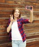 Menina bonita que toma o autorretrato da imagem no smartphone fotos de stock