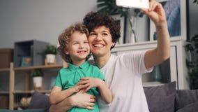 Menina bonita que toma o selfie com o filho bonito que ri tendo o smartphone da terra arrendada do divertimento