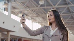 Menina bonita que toma o selfie no terminal de aeroporto Mulher de negócio nova na alameda com telefone Imagem de Stock Royalty Free