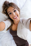 Menina bonita que toma um autorretrato com seu smartphone no hom foto de stock royalty free