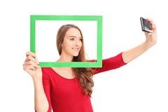Menina bonita que toma um selfie atrás da moldura para retrato Foto de Stock Royalty Free