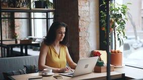 Menina bonita que trabalha com o laptop no café que datilografa olhando a tela filme