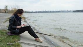 Menina bonita que trabalha na tabuleta na praia video estoque