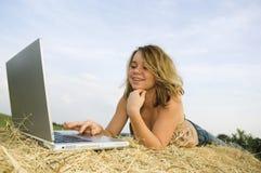 Menina bonita que trabalha no portátil Fotos de Stock