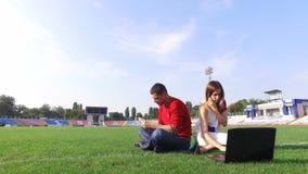 A menina bonita que trabalha no portátil, homem lê um livro no estádio vídeos de arquivo