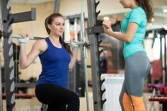 Menina bonita que usa o barbell no gym O instrutor mantém o relógio sobre ela Foto de Stock Royalty Free
