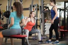 Menina bonita que usa o barbell no gym O instrutor mantém o relógio sobre ela Fotos de Stock Royalty Free
