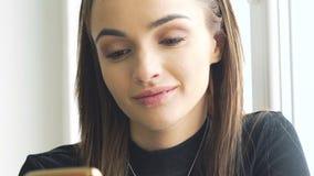 Menina bonita que usa o smartphone perto da janela lentamente vídeos de arquivo