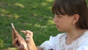 A menina bonita que usa um smartphone está escrevendo uma letra em um banco em um parque verde bonito Movimento lento novo vídeos de arquivo