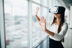 A menina bonita que usa vidros da realidade virtual aproxima a janela brilhante com opinião do arranha-céus fora Mulher de negóci fotografia de stock