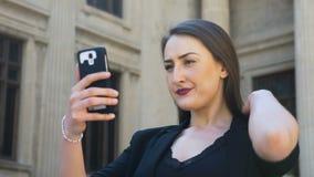 Menina bonita que verifica sua composição e que toma o selfie usando o smartphone video estoque