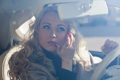 Menina bonita que verifica sua composição em seu carro Foto de Stock Royalty Free