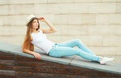 Menina bonita que veste um chapéu e calças de brim de palha do verão foto de stock royalty free