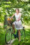 Menina bonita que veste um vestido branco agradável que tem o divertimento no parque com bicicleta Conceito exterior saudável do  Fotos de Stock