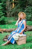 A menina bonita que vestem o vestido azul e o chapéu recolhem flores na cesta na madeira Fotos de Stock Royalty Free