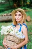 A menina bonita que vestem o vestido azul e o chapéu recolhem flores na cesta na madeira Foto de Stock