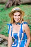 A menina bonita que vestem o vestido azul e o chapéu recolhem flores na cesta na madeira Imagens de Stock Royalty Free