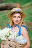 A menina bonita que vestem o vestido azul e o chapéu recolhem flores na cesta na madeira Fotografia de Stock