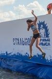 A menina bonita salta na água na competência do extrim Imagem de Stock