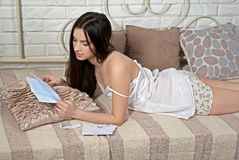 Menina bonita semi-nua na cama que lê uma letra Fotografia de Stock