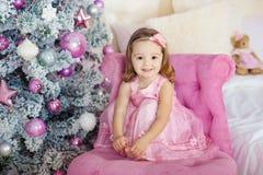 A menina bonita senta-se e levanta-se em uma cadeira grupo festivo do abeto do fundo de fogos brilhantes Sorri delicadamente Imagens de Stock