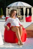 A menina bonita senta-se em um pufe vermelho macio Foto de Stock