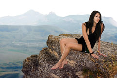 A menina bonita senta-se em uma rocha imagens de stock