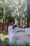 A menina bonita senta-se na pedra cinzenta enorme Imagens de Stock Royalty Free