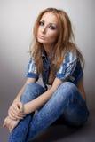 A menina bonita senta-se nas calças de brim e no revestimento Imagens de Stock Royalty Free