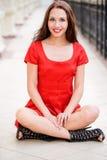 A menina bonita senta-se no assoalho Imagem de Stock